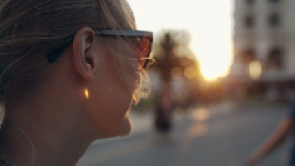 Woman in sunglasses looking into distance during sunset