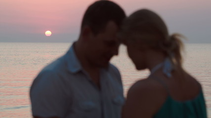 Loving couple on the beach during sunset