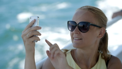 Woman making selfie with smatphone on the boat