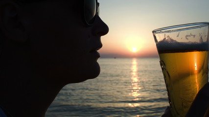Woman drinking beer on beach at sunset