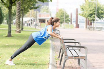 Smiling athletic woman doing push ups in the street, healthy lif