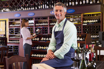 Smiling worker sitting on table in wine shop