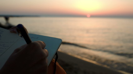 Woman making notes sitting by sea at sunset