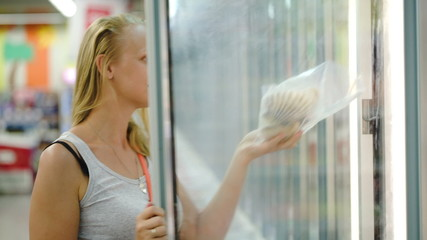 Woman taking product from fridge in store