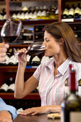 Curious woman tasting glass of red wine in wine shop