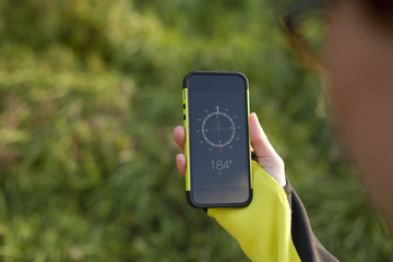 Female hand holding digital compass in the nature