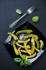 Sliced and grilled avocado with salt over black wooden surface