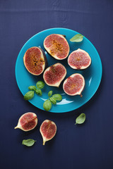 Ripe sliced figs on a glass plate, above view, vertical shot