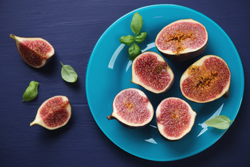 Above view of a glass plate with sliced fig fruits, studio shot