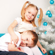 Happy kids cuddling near Christmas tree.