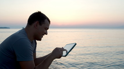 Young man by the sea typing message on pad