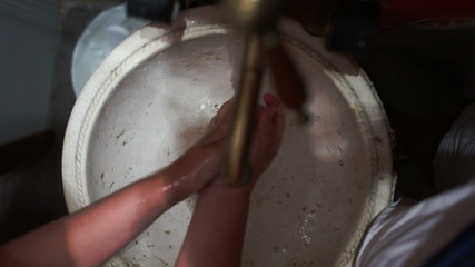 Woman washing hands in old vintage sink