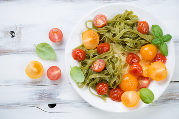 Boiled tagliatelle with different fried tomatoes and basil