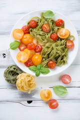 Boiled tagliatelle and various roasted tomatoes, view from above