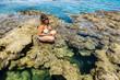 Girl in bikini posing on a coral reef in the Red Sea