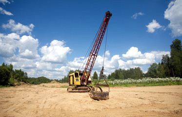 Excavator standing on sand near forest on summer day