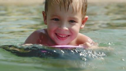 Boy learning to swim on board