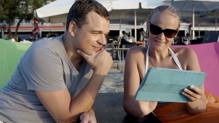 Man and woman with tablet computer on the beach