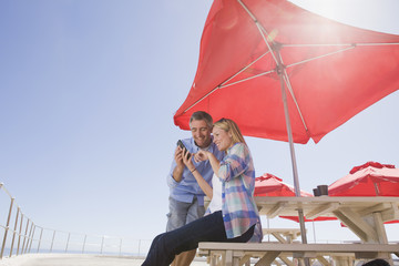 Smiling couple using cell phone under umbrella at waterfront table