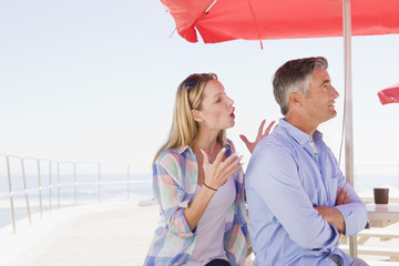 Couple arguing under umbrella at waterfront table
