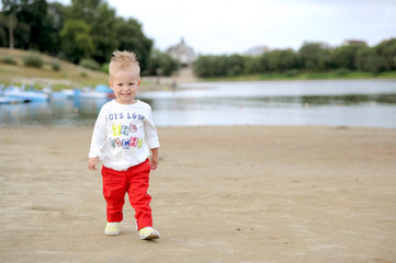 the kid in red trousers plays on the sands at the river