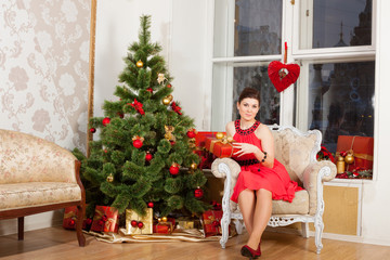 girl sits near New-Year's tree