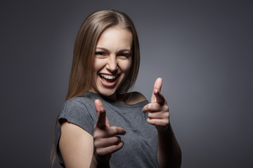 Smiling woman with okay gesture on dark grey