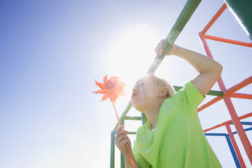Boy blowing pinwheel on monkey bars at playground