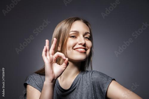 Smiling woman with okay gesture on dark grey - 71606419