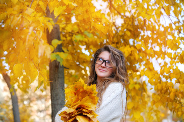 Young smiling girl-student in glasses close up against yellow au