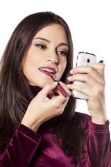 young woman uses her smartphone as a makeup mirror