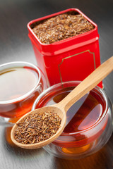 rooibos in wooden spoon, two tea cups and tea tin box