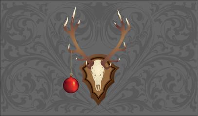 Hirschgeweih mit Weihnachtskugel vor garuer Tapete