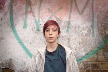 portrait of a teenage boy in front of a graffiti