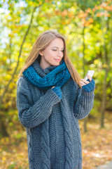Young woman using a mobile outdoors in autumn