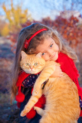 Little girl holding a big red cat