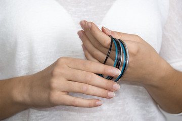 Young woman hand with jewelry, cyan, silver and black rings.