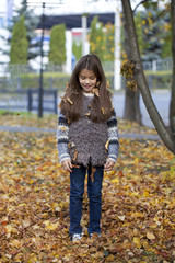 Young beautiful little girl with yellow leaves in autumn park