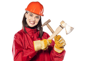 Crazy young helmeted woman worker holding axe and hammer
