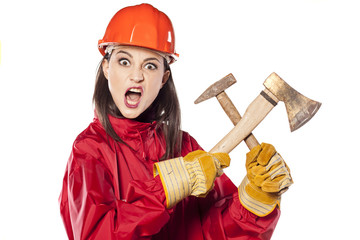Funny young helmeted woman worker holding axe and hammer