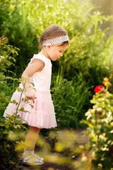 Little Girl Standing in a Garden