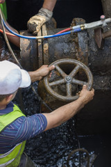 Industrial worker turning a valve on a large pipe