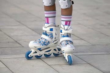 Close-up view of female legs in roller blades.