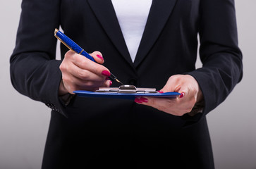 Businesswoman writing in ink on the clipboard