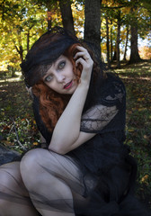 Pretty redhead wearing black dress and black veil in forest