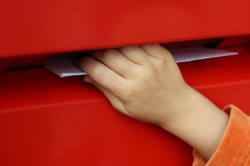 children's hand putting letters mailbox