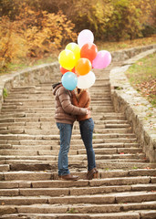 Couple in love hiding behind balloons to kiss