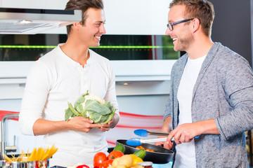 Freunde kochen Gemüse und Fleisch zuhause in Küche