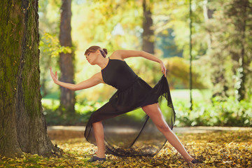 Ballerina dancing in nature among autumn leaves.