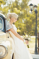 Beautiful bride with bouquet of flowers in white dress